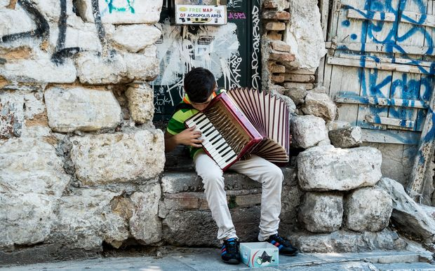 A Young street musicians plays the piano accordion on a street in the Plaka district of Athens.