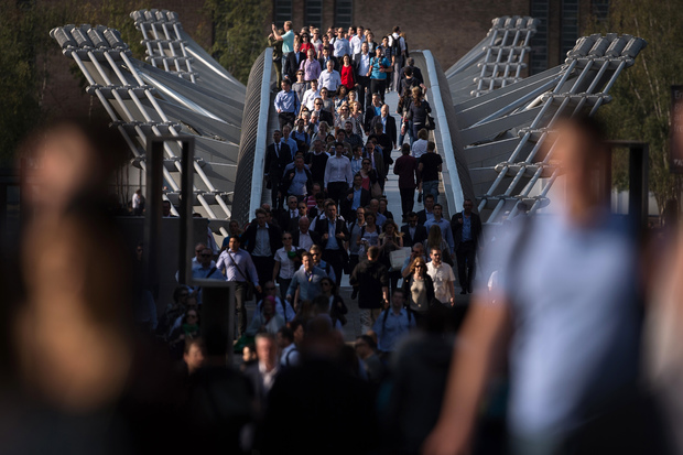 Commuters cross the river Thames using the Millennium footbridge during a tube strike in London.