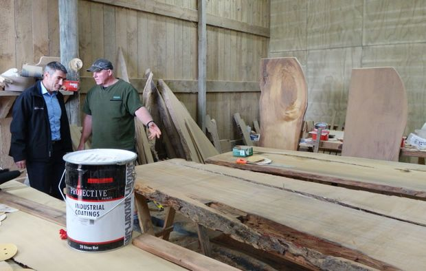 Nathan Guy examines kauri slabs and table tops with Kaihu mill and gallery owner Nelson Parker.