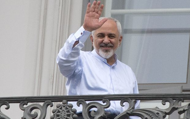Iranian Foreign Minister Mohammad Javad Zarif waves from a balcony of the Palais Coburg Hotel where the Iran nuclear talks meetings were being held in Vienna.