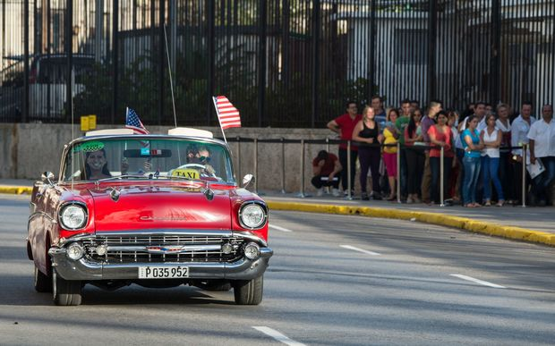 A vintage car with US flags drives by the US embassy in Havana as the countries formally resume diplomatic relations.