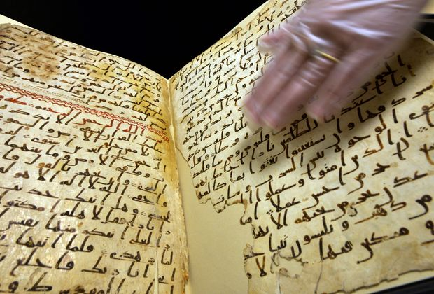 Marie Sviergula, conservator of the University of Birmingham holds a Koran manuscript thought to be at least 1,370 years old.
