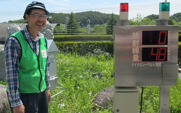 Japanese man in fluoro vest stands beside stainless steel box with digital display