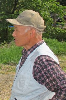 Farmer stands outside in cap and check shirt