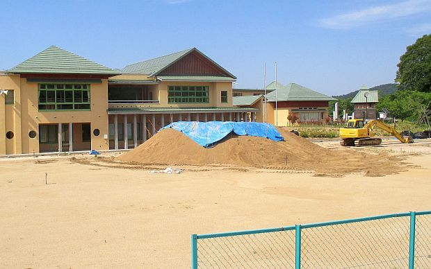2 storey school buildings with a digger and pies of dusty earth in front