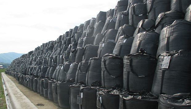 Huge black storage bags piled more than six high stretch as away as far an the eye can see.
