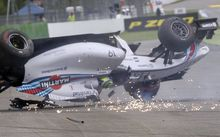 A Formula One car rolls after crashing.