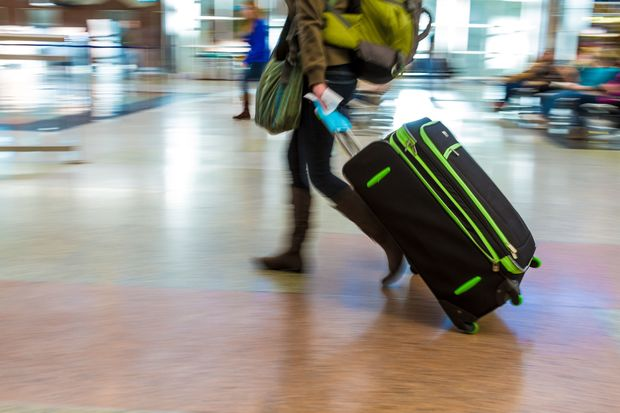 A woman with a backpack pulls a suitcase through an airport.