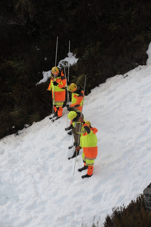 A photo released by police shows search and rescue workers near the site of the avalanche in Fiordland National Park.