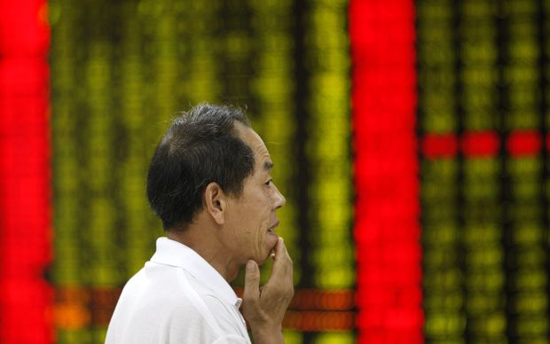An investor looks at prices of shares (red for price rising and green for price falling) at a stock brokerage house in Huaibei city, Anhui province, China, 27 July 2015.
