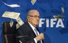 Dollar bills rain down on FIFA president Sepp Blatter, at a media conference in Zurich. A man posing as a journalist had thrown the money at him.