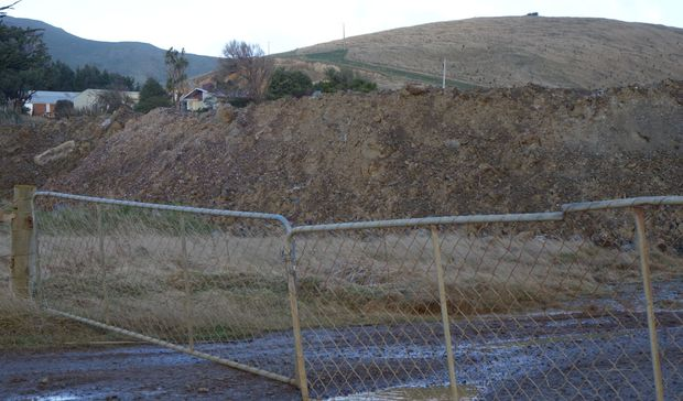 The quarried dirt 'overburden' dumped in large piles in front of the quarry pit.
