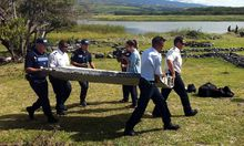 Police carry debris from an aircraft found on the Indian Ocean island of La Reunion.