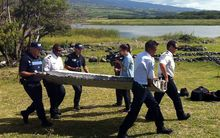 Police carry a piece of debris from an aircraft found in the coastal area of Saint-Andre de la Reunion, in the east of the French Indian Ocean island of La Reunion.