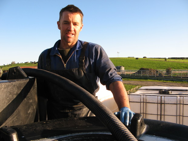 Andrew McPherson beside his colostrum tanks.