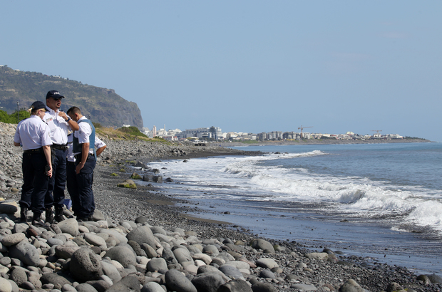 Police officers inspect metallic debris on the French Reunion Island in the Indian Ocean.