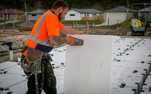 A builder cutting polystyrene used for insulation and foundation footings on a new home in Upper Hutt.