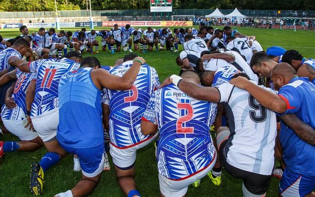 The Fiji and Samoa teams pray after their Pacific Nations Cup title decider.