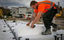 A builder installing polystyrene used for insulation and foundation footings on a new home in Upper Hutt.