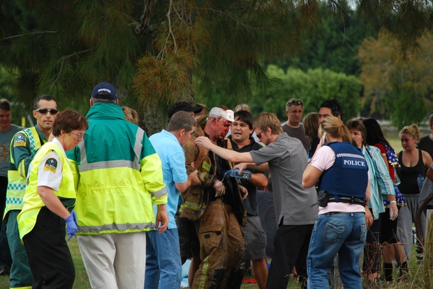 Tamahere people and emergency service people attending to a burnt fireman on the Tamahere School grounds.