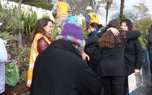 Tracey Keane-Harvey (right, holding placard) is hugged by a supporter at a workplace safety vigil in Nelson.