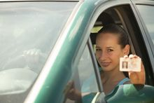 woman in car holding driver licence