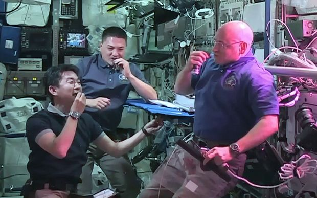 Astronauts (from left) Kimiya Yui, Kjell Lindgren and Scott Kelly eat red romaine lettuce grown on board the International Space Station.