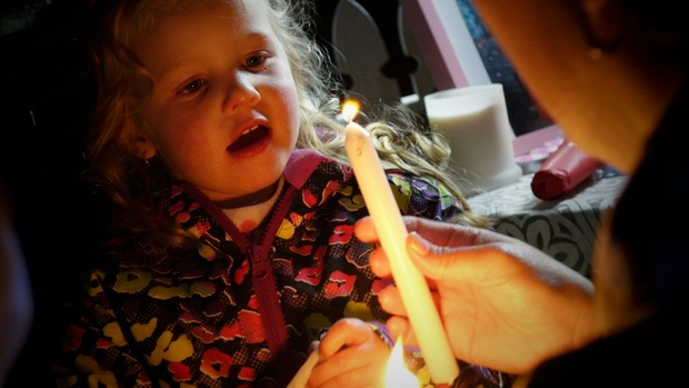 A child attends the candlelit vigil in memory of four-year-old Maggie Renee Watson.