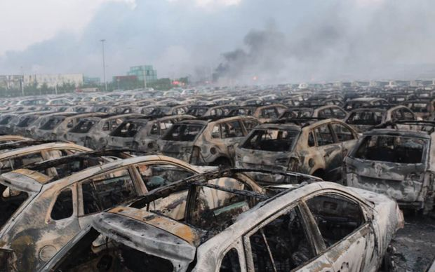 Charred new cars in this nearby parking lot were reduced to blackened shells.