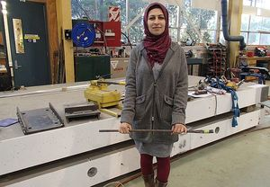 Engineering student Zeinab Chegini holds a short length of the wire cable that is used as a post-tensioning tendon. The tendons run the 10-metre length of each of the concrete slabs behind her, that make up the bridge superstructure.