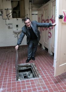 Ian Reid from Auckland Council's property team, holding open the lid to expose the original sewer under the now-closed Wellesley Street East women's conveniences.
