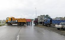 Trucks block the entrance of a Noumea blockade as part of a protest that has ground the city to a standstill