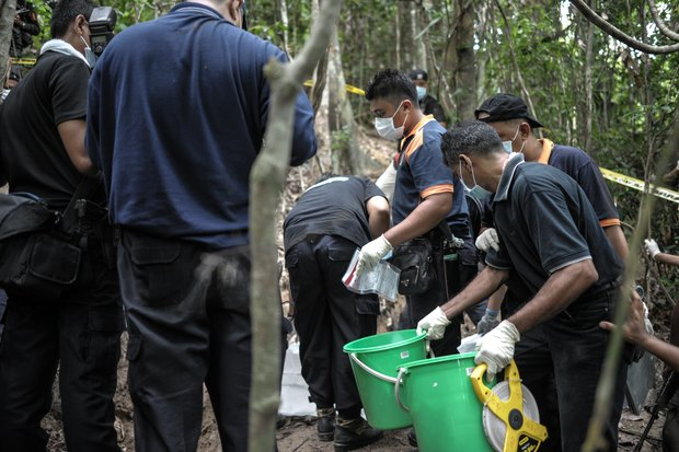 A Royal Malaysian Police forensics team handles exhumed human remains at a grave site near an abandoned migrant camp used by people-smugglers.