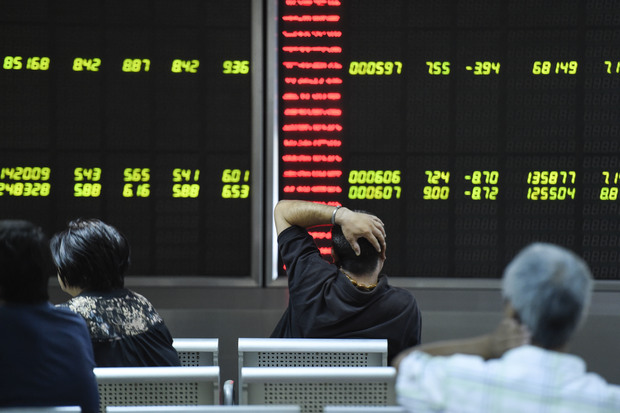 Investors look at screens showing stock market movements at a securities company in Beijing.