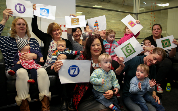 Labour's spokesperson for Women, Sue Moroney (holding number 7), and a group of mothers supporting thenew paid parental leave bill.