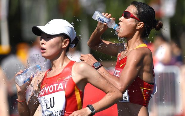 Liu Hong (R) and Lu Xiuzhi of China take on water while competing in the 20km race walk at the 2015 World Championships.