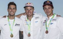 Erik Heil (centre) stands on the podium at the Olympic test regatta next to Blair Tuke (left) and Thomas Plößel.