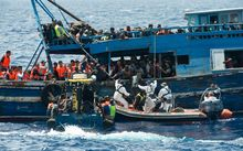 Migrants on a wooden boat during a rescue operation in the Mediterranean sea on August 26, 2015. At least 55 dead bodies were found. Almost all of the victims were found in the hold of a wooden boat found drifting precariously off the Libyan coast. They had choked to death on gas fumes.