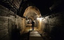 "Men walk in underground galleries, part of Nazi Germany ""Riese"" construction project under the Ksiaz castle in the area where the ""Nazi gold train"" is supposedly hidden underground"