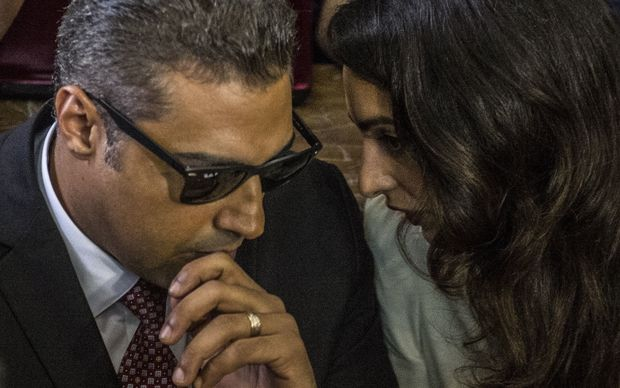 Al-Jazeera journalist, Canadian Mohamed Fahmy (L), talks to human rights lawyer, Amal Clooney (R), during the retrial in the capital Cairo on August 29, 2015