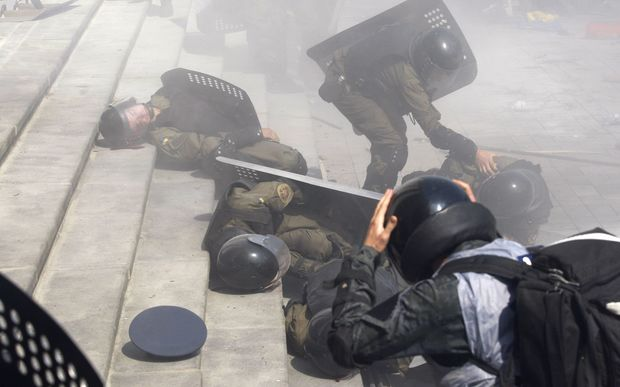 Police help injured comrades after clashes with protesters outside Ukraine's parliament.