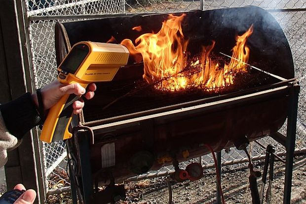 A laser thermometer reads the temperature as samples of plants are incinerated on the plant barbecue.