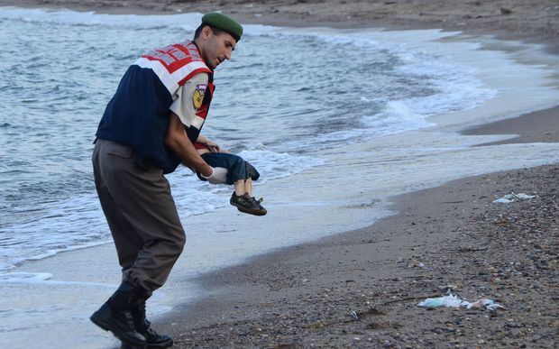 A Turkish police officer carries the 3-year-old's dead body off the beach in Bodrum, southern Turkey.