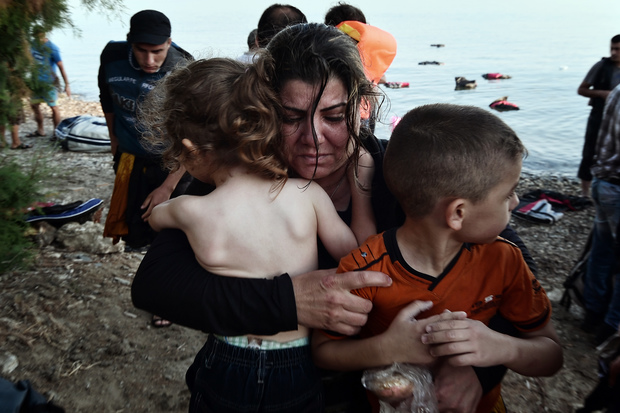 A Syrian woman holds her children as they arrive on an overcrowded dinghy on a beach near the port on the Greek island of Kos on 15 August.