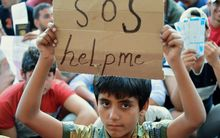 "A migrant boy holds a sign reading ""SOS help me"" as he sits with other migrants in front of the railway station in Budapest."