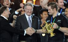 Dubbed the three-way handshake: IRB boss Bernard Lapasset, PM John Key and All Blacks captain Richie McCaw with the Webb Ellis Cup at the conclusion of the 2011 Rugby World Cup.