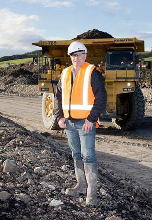 Bathurst Chief Executive stands in hard hat and gumboots near heavy truck and coal.