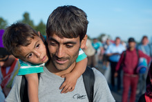 Hundreds of refugees from Syria, Iraq and Africa walk along the motorway towards the Austrian border.