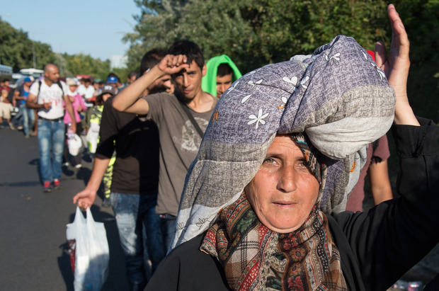Amina Hmeid - from Deraa in Syria - carries her possessions on her head, as she and hundreds of other refugees and migrants attempt to walk to Austria.