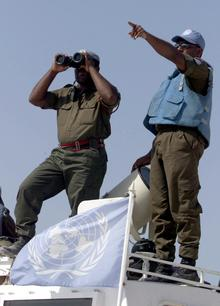 A Fijian UN peacekeeper looks through binoculars at an Israeli post from the Al-Labbouneh hill near Naqoura on the Mediterranean coast 30 July 2000 where fifty Fijian troops took up position.